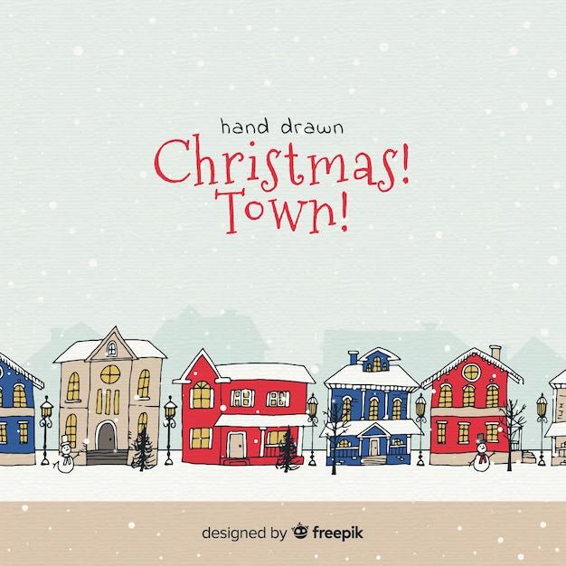 Gezeichnetes design der weihnachtsstadt in der hand Kostenlosen Vektoren