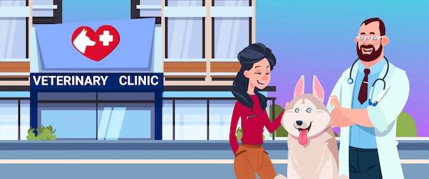 Glückliche frau mit hund und tierarzt doctor over veterinary clinic exterior Premium Vektoren