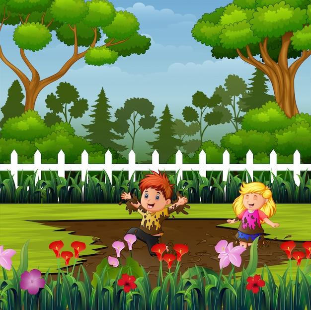 Glückliche kinder, die eine schlammpfütze im park spielen Premium Vektoren
