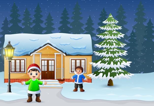 Glückliche kinder, die vor dem schneienden haus spielen Premium Vektoren