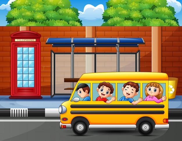 Glückliche kinder fahren mit dem schulbus Premium Vektoren
