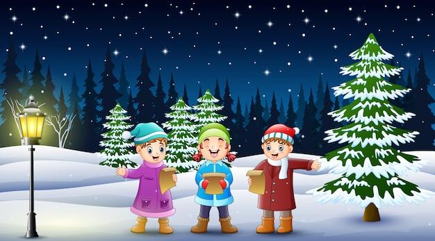 Glückliche kindergruppe, die im schneebedeckten garten singt Premium Vektoren