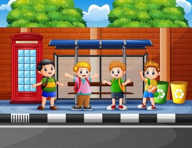 Glückliche schulkinder an der bushaltestelle Premium Vektoren