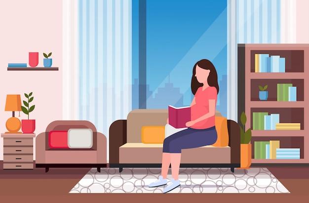 Glückliche schwangere frau, die auf der couch sitzt, die buchmädchen liest, das ihr stoßmädchenschwangerschaftskonzept moderner wohnzimmerinnenraum in voller länge horizontal hält Premium Vektoren