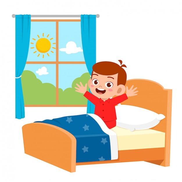 Glücklicher netter kleinkindjunge wachen morgens auf Premium Vektoren