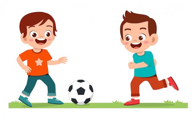 Glücklicher süßer kleiner junge spielt fußball Kostenlosen Vektoren