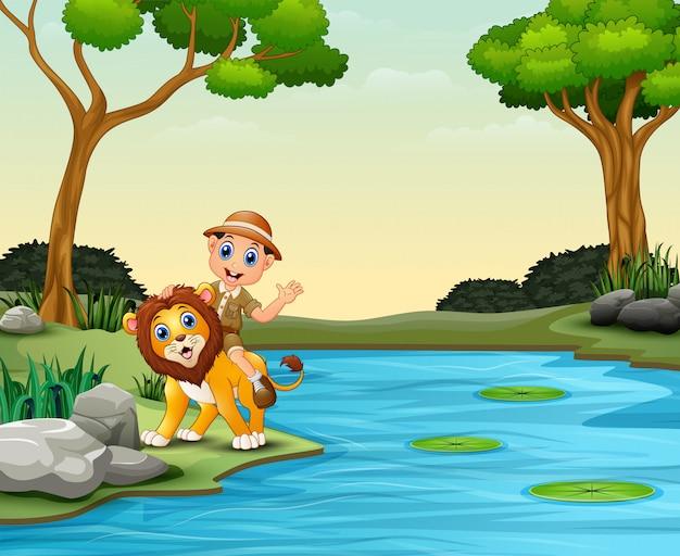Glücklicher tierpflegerjunge und -löwe nahe einem fluss Premium Vektoren