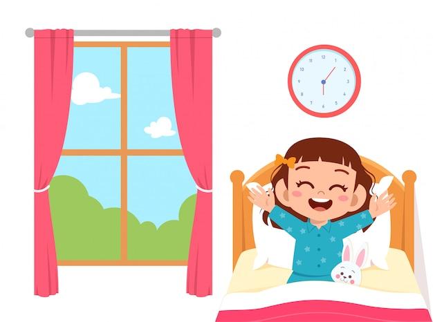 Glückliches nettes kleinkindmädchen wachen morgens auf Premium Vektoren