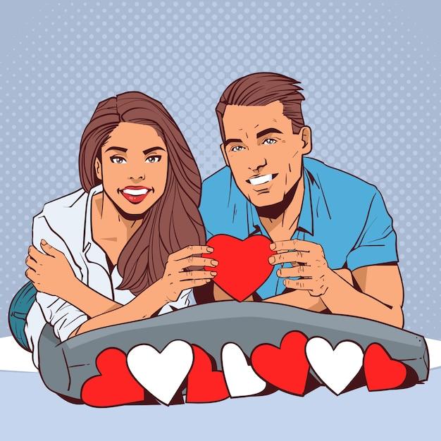 Glückliches paar, das rotes herz-lächelnden mann und verliebte frau über komischem pop-art style valentine day celebration concept hält Premium Vektoren