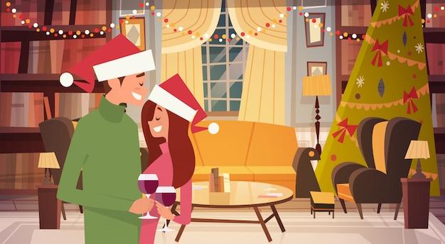 Glückliches paar in santa hats umarmen im wohnzimmer für frohe weihnachten und ein glückliches neues jahr dekoriert Premium Vektoren