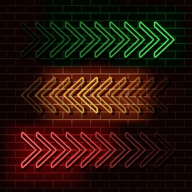 Grüne, gelbe und rote neonpfeile auf einer backsteinmauer. Premium Vektoren