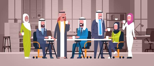 Gruppe arabische geschäftsleute trinken tee oder kaffee, die zusammen am schreibtisch im modernen büro-moslemischen arbeitskraft-team at break sitzen Premium Vektoren