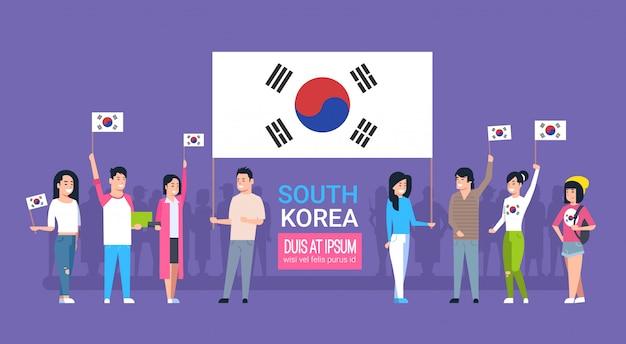 Gruppe junge leute, die koreanische flaggen-südkorea-jugend-männer und frauen halten Premium Vektoren