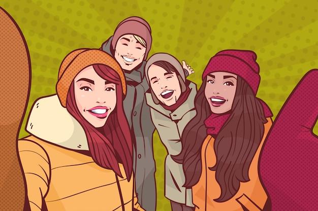Gruppe junge leute, die selfie-foto-tragende winter-kleidung über bunter retrostil-hintergrund-mischungs-rennen-mann machen und das glückliche lächeln der frau nehmen selbstporträt Premium Vektoren