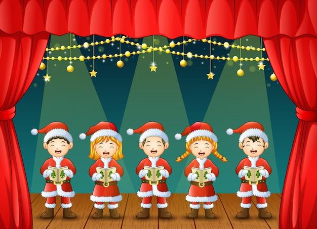 Gruppe kinder, die weihnachtsliede auf dem stadium singen Premium Vektoren