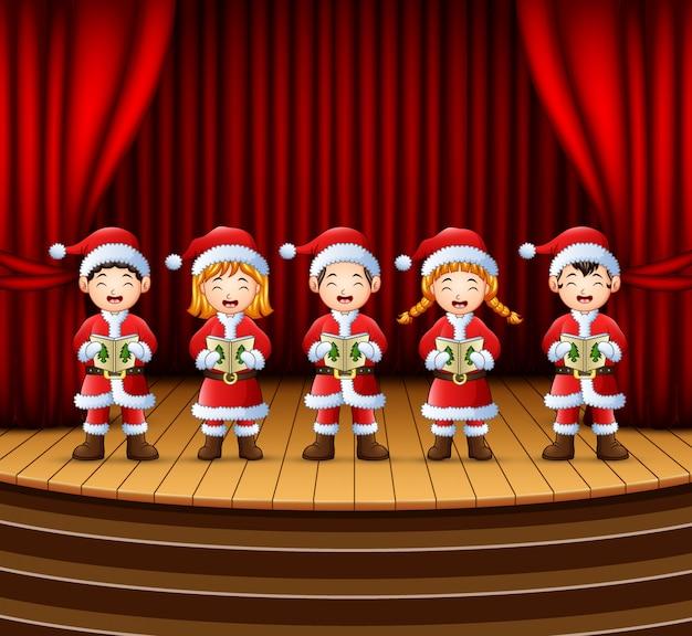 Gruppe kinder, die weihnachtslieder auf der bühne singen Premium Vektoren