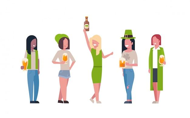 Gruppe mischungs-rennfrauen im grünen kleidungs-getränk-bier, welches den glücklichen tag st. patricks lokalisiert feiert Premium Vektoren