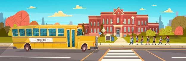 Gruppe schüler-mischungs-rennen, das zum schulgebäude vom gelben bus geht Premium Vektoren