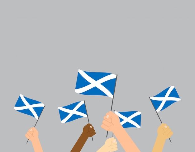Hände halten schottland flaggen Premium Vektoren