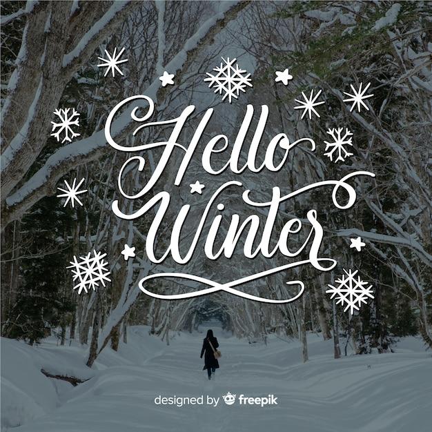 Hallo winter schriftzug mit wald und schnee Kostenlosen Vektoren