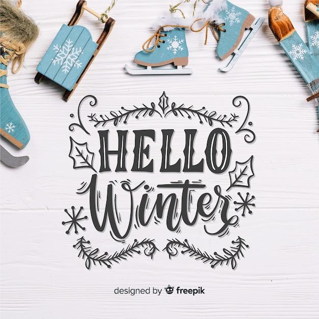 Hallo winterbeschriftung mit erschütterungen auf hölzernem brett Kostenlosen Vektoren