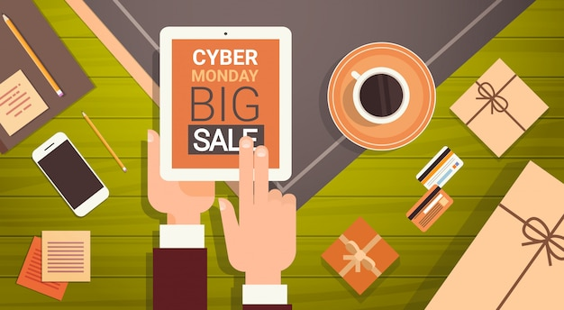 Hand, die digital-tablet mit cyber monday big sale message, on-line-einkaufsfahne hält Premium Vektoren