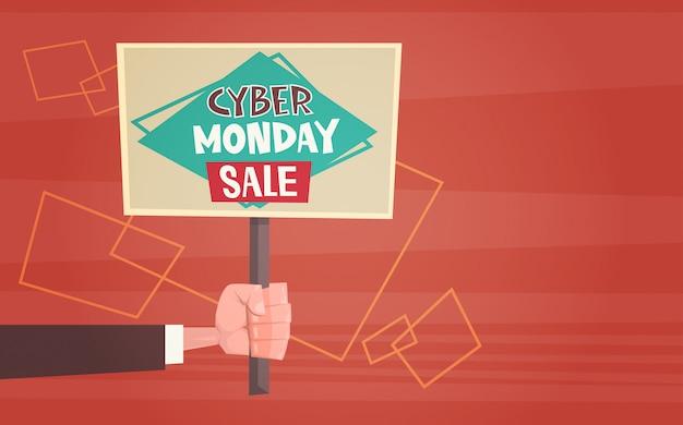 Hand, die fahne mit text cyber monday sale deals design online hält Premium Vektoren
