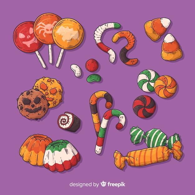 Hand gezeichnete halloween-süßigkeitssammlung auf purpurrotem hintergrund Kostenlosen Vektoren