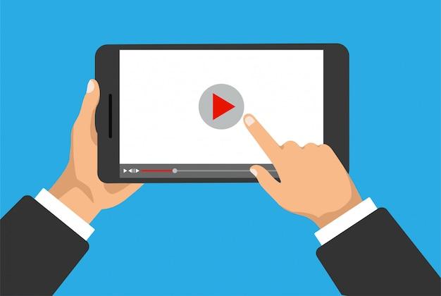 Hand hält telefon oder digitales tablet mit videoplayer auf einem display. klicken sie mit dem finger auf das wiedergabesymbol. filmkonzept. Premium Vektoren