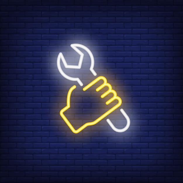 Hand mit schraubenschlüssel leuchtreklame Kostenlosen Vektoren