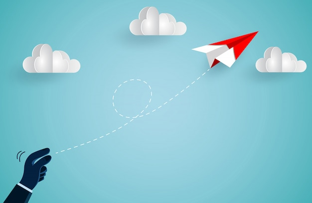 Handmensch, der das rote papierflugzeug in den himmel warf, während er über eine wolke flog Premium Vektoren