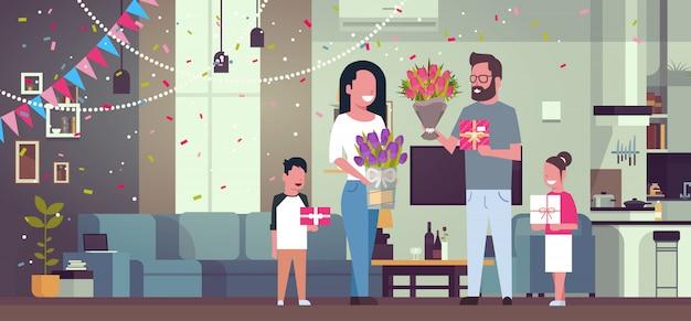 Happy family gratulieren mutter mit frauentag 8. märz mit geschenken und blumen im wohnzimmer Premium Vektoren