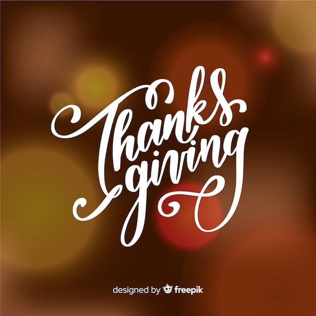 Happy thanksgiving-schriftzug auf unscharfen hintergrund Kostenlosen Vektoren