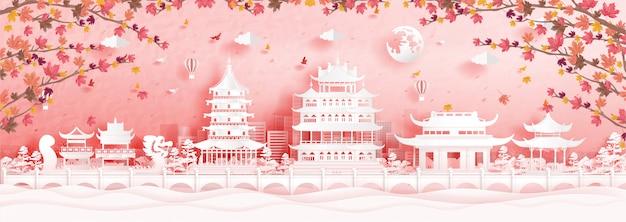 Herbst in hangzhou, china mit fallenden ahornblättern und weltberühmten wahrzeichen in papierschnittartillustration Premium Vektoren