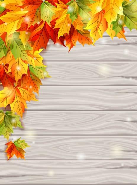 Herbstlaub auf dem hintergrund des hellen hintergrundes der hölzernen bretter Premium Vektoren
