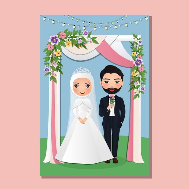 Hochzeitseinladungskarte der niedlichen muslimischen paarkarikatur der braut und des bräutigams unter dem torbogen, der mit blumen verziert wird Premium Vektoren