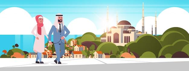 Ic paar, das im freien arabische mannfrau geht, die traditionelle kleidung arabische zeichentrickfiguren über nabawi moschee gebäude muslimischen stadtbild schönen meer hintergrund horizontal trägt Premium Vektoren
