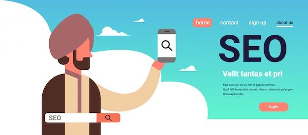 Indischer mann, der das suchmaschinenoptimierungsinternet des smartphone seo sucht konzept verwendet Premium Vektoren