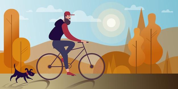 Junger bärtiger mann, der fahrrad mit einem hund im herbstpark fährt. Premium Vektoren
