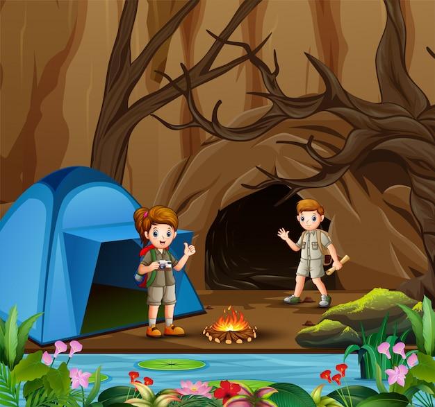 Junger pfadfinderjunge und -mädchen in der campingzonenszene Premium Vektoren