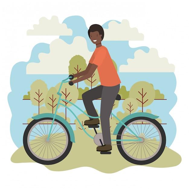 Junger schwarzer mann im fahrrad im park Premium Vektoren