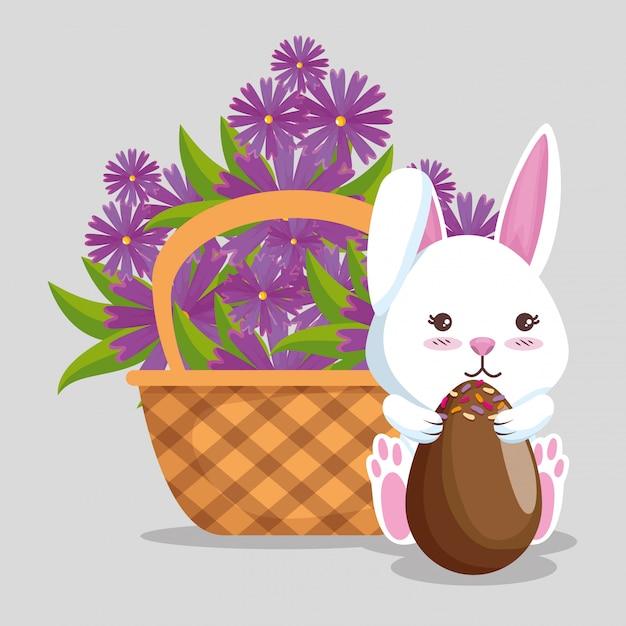 Kaninchen mit schokoladeneiern und -blumen innerhalb des korbes Kostenlosen Vektoren