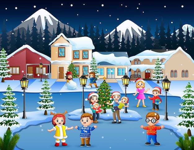 Karikatur des glücklichen kindes und der familie, die im schneienden dorf spielt Premium Vektoren