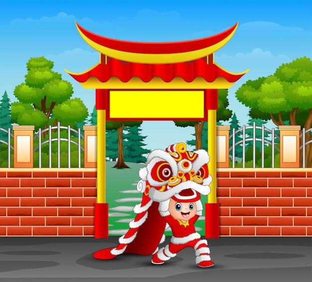 Karikatur des kindes chinesischen drachetanz spielend Premium Vektoren
