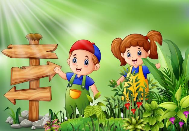 Karikatur des kleinen landwirts stehend neben wegweiser Premium Vektoren