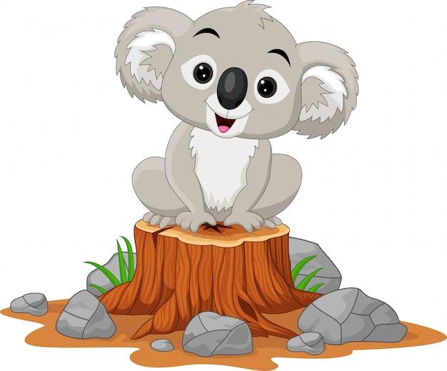 Karikaturbaby koala, der auf baumstumpf sitzt Premium Vektoren