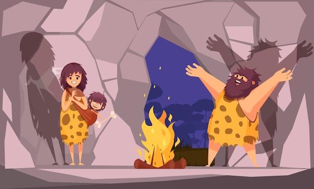 Karikaturillustration mit höhlenmenschenfamilie gekleidet in tierfell gesammelt um das feuer in der höhle Kostenlosen Vektoren
