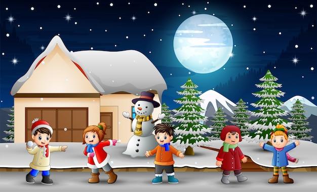 Karikaturkinder, die vor dem schneienden haus singen Premium Vektoren