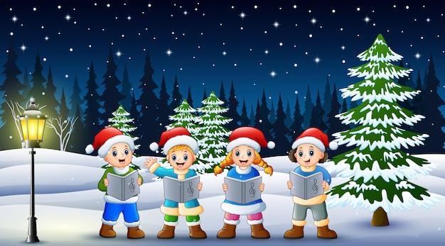 Kinder singen weihnachtslieder in winterkleidung und nikolausmütze mit schneebedeckten kiefern Premium Vektoren
