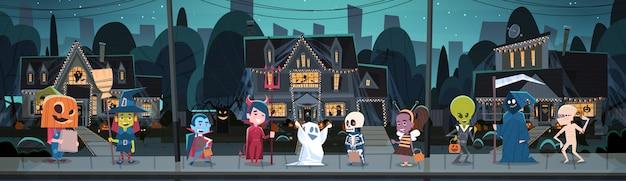 Kinder, welche die monster-kostüme gehen in stadttricks oder festlichkeits-glückliches halloween-fahnen-feiertags-konzept tragen Premium Vektoren